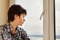 Beautiful woman looks outdoor through a window Stock Image