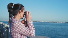 Beautiful Woman Looks At River Through Viewfinder Retro Camera Standing On Embankment