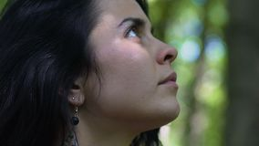 Beautiful woman looks up walking outdoors, unity with nature, oneness beauty