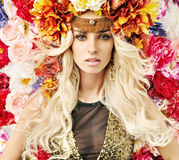 Beautiful woman with lots of colorful flowers royalty free stock image