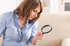 Beautiful woman with loupe Stock Photography