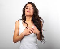 Beautiful woman in love holding herself chest and heart two hand. S with enjoying smiling face and thinking about emotion relationship on white background stock image