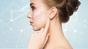 Beautiful woman with low poly projection on cheek. Beauty, technology and people concept - beautiful young woman pointing finger to her skin over blue background royalty free stock images