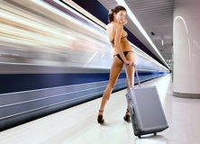 Beautiful woman with luggage in subway stock image
