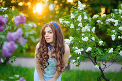 Beautiful woman in a lush garden in the spring lilac Stock Photography