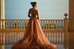 Beautiful woman in luxurious ballroom dress with tulle skirt and lacy top standing on the large balcony with sea view. Back view stock photo