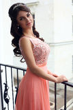 Beautiful woman in luxurious dress posing on balcony Stock Photos