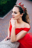 Beautiful woman in a luxurious red dress, close-up. Young woman in a luxurious red dress on the architecture background, close-up Royalty Free Stock Photo