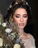Beautiful woman in a luxurious wedding dress. Portrait of the bride with a large bouquet.