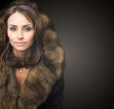 Beautiful woman in luxury fur coat. On a dark background royalty free stock photo