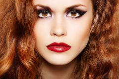Beautiful woman with luxury make-up and curly hair. Close-up portrait of beautiful fashion woman model with luxury evening make-up, dark eyeshadows, bloody lips stock photo