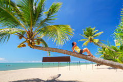 Beautiful woman lying on the amazing palm tree Royalty Free Stock Image