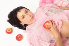 Beautiful woman lying with apple. Beautiful woman with an apple. Brunette in pink with an apple in the hand lying on a white background Stock Photos