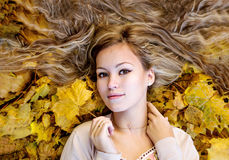 Beautiful woman lying with autumn leaves Stock Photo