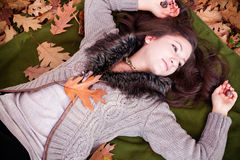 Beautiful woman  lying on autumn leaves in park Royalty Free Stock Photo