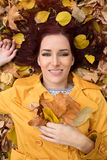 Beautiful woman lying in autumn leaves Royalty Free Stock Photo