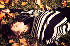 Beautiful woman lying in autumns leaves Stock Image