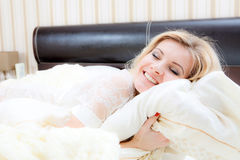 Beautiful woman lying in bed Stock Photos