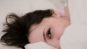 Beautiful woman lying in bed. Brunette girl looks out under a blanket. Smiling female in the morning at light apartment. Royalty Free Stock Photography