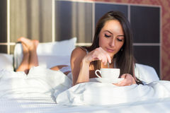 Beautiful woman lying in bed and drinking coffee or tea the morning Royalty Free Stock Photo
