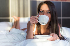 Beautiful woman lying in bed and drinking coffee or tea the morning Stock Photos