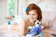 Beautiful woman lying on the bed with flowers Stock Photo