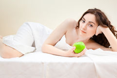 Beautiful woman lying in bed with green apple Royalty Free Stock Photography