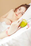 Beautiful woman lying in bed with green apple Stock Photo