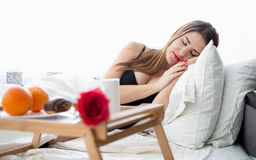 Beautiful woman lying in bed and having breakfast at hotel room Stock Photo