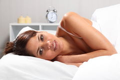 Beautiful woman lying in bed head on pillow Stock Image