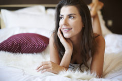 Beautiful woman lying on bed Stock Images