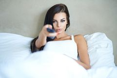 Beautiful woman lying in bed watching television Stock Photo