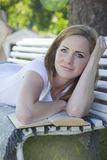 Beautiful woman reading. A beautiful woman lying on a bench outside in a park on a summer day. The woman is looking into the camera smiling with her head leaning Royalty Free Stock Photos