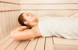 Beautiful woman lying on bench at sauna Royalty Free Stock Photography