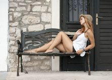 Beautiful woman lying on bench at the stone building Royalty Free Stock Photos