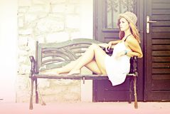 Beautiful woman lying on bench at the stone building Royalty Free Stock Image