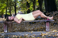 Beautiful woman lying on a bench Stock Images