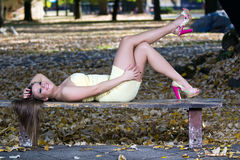Beautiful woman lying on a bench Stock Photos