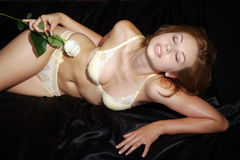 Beautiful woman lying on black satin Stock Photos