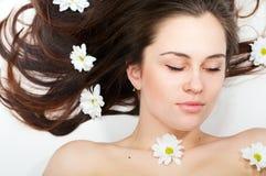 Beautiful woman lying in chamomiles Stock Photos