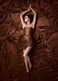 Beautiful woman lying on a chocolate fabric. Stock Photos