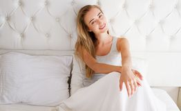 Beautiful woman lying on a comfortable bed looks at you in the morning in an hotel room or home bedroom stock image