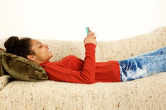 Beautiful woman lying on couch with smart phone Stock Photo