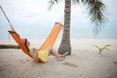 Woman lying on the cradle at the beach. Beautiful woman lying on the cradle at the beach by the sea stock photography