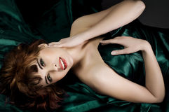 Beautiful woman lying on dark green  silk Stock Images