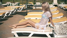 Beautiful woman lying on deck chair Young woman relaxes by the pool,video clip stock footage