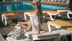 Beautiful woman lying on deck chair Young woman relaxes by the pool,video clip stock video