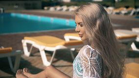 Beautiful woman lying on deck chair Young woman relaxes by the pool,video clip stock video footage