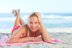 Beautiful woman lying down on the beach Stock Image