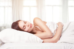 Beautiful woman lying down in bed Royalty Free Stock Photography